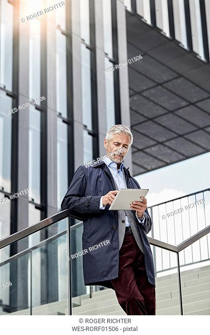 Portrait of mature businessman standing on stairs in front of modern office building using tablet