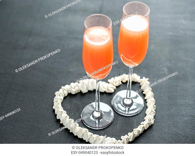 Two bellini cocktails inside of meringue heart
