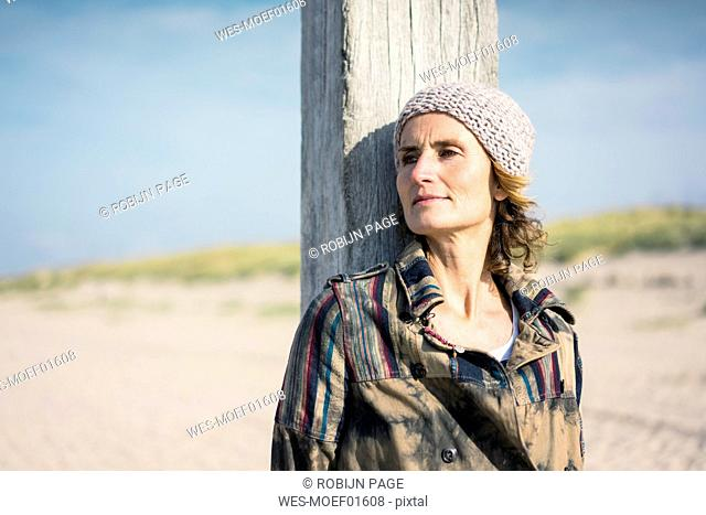 Woman with woolly hat leaning on wood pole