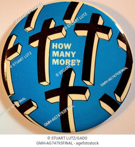 An anti-Vietnam War protest pin that features a blue background and black and white images of crosses, it also features the text 'How many more?', 1970