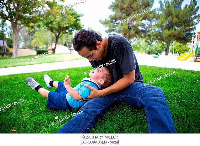 Male toddler playing with older adult brother in park