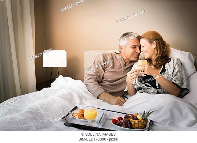 Smiling couple having breakfast in bed