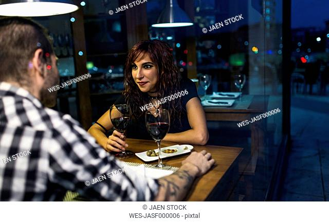 Young couple drinking wine in bar at night