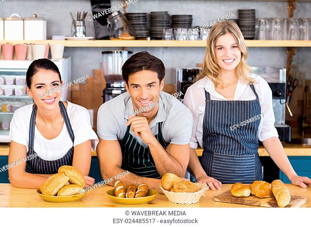 Smiling waiter and two waitresses leaning on counter