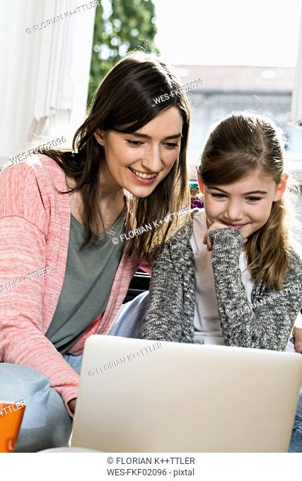 Smiling mother and daughter using laptop