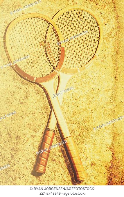 Old sports equipment still life photo of two vintage tennis racquets on grunge cerment playing surface
