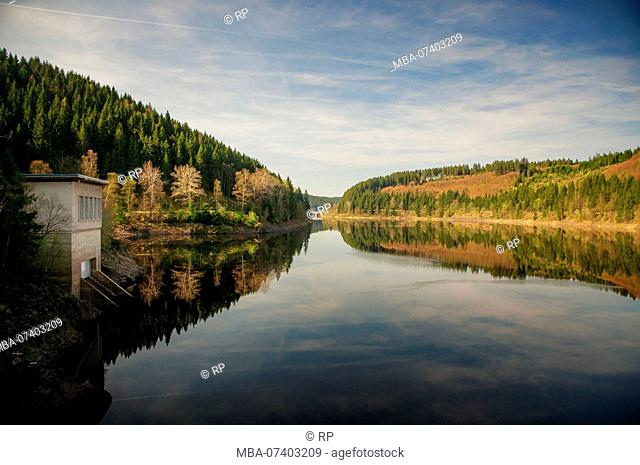 Summer view of a mountain lake with rocks in the foreground. Okertalsperre, Okerstausee, National Park Harz in Germany