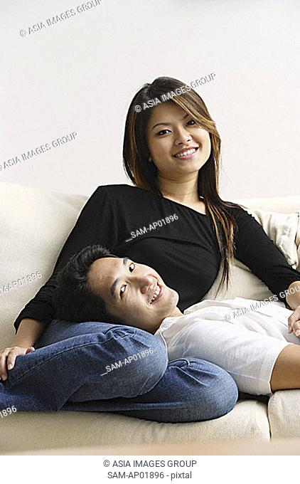 Couple on sofa, man lying on woman's lap, both smiling at camera