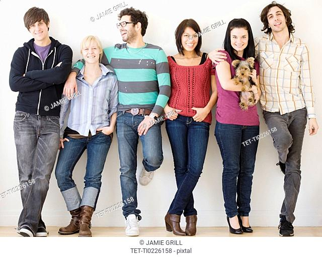 Group of friends leaning on wall