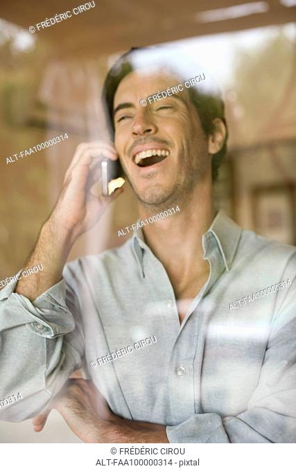 Man using cell phone bursting out laughing