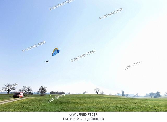 Motor-Paraglider starting off from a meadow, Penzberg, Bavaria, Germany