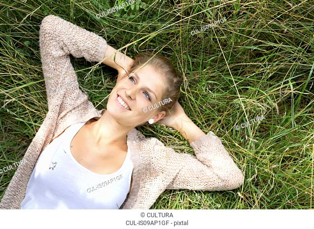 Young woman laying in grass, hands behind head
