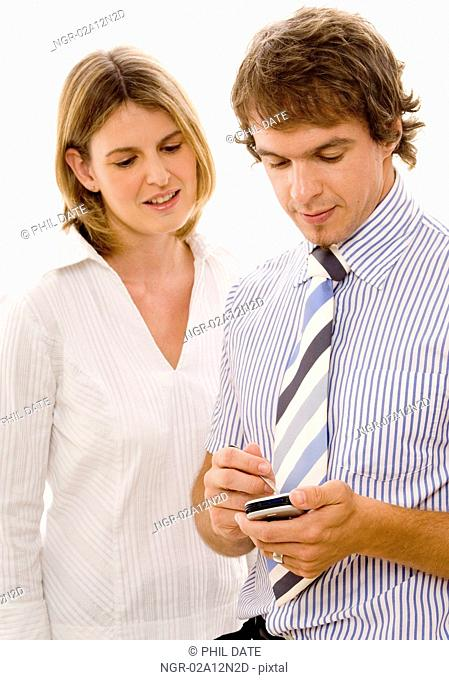Businessman using a personal data assistant with a businesswoman standing beside him
