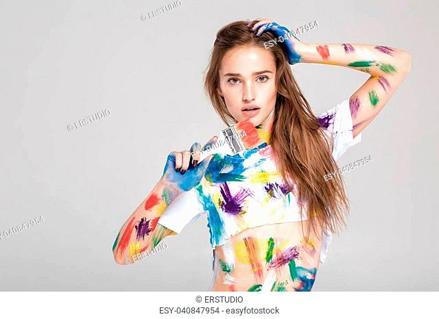 beautiful young woman with paint brush is dirty in multicolored paint