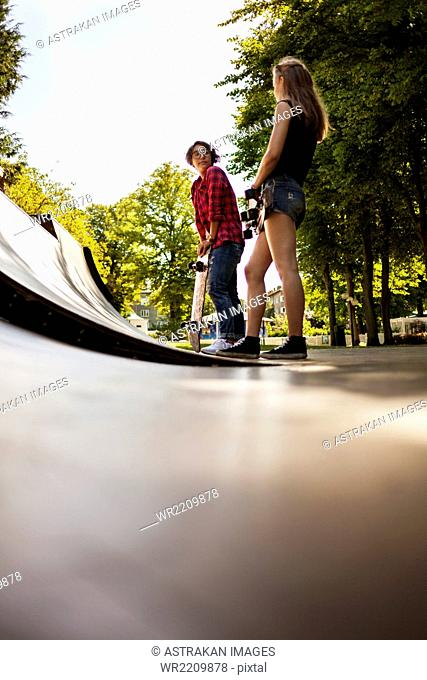 Low angle view of girls holding skateboard and standing on ramp at park