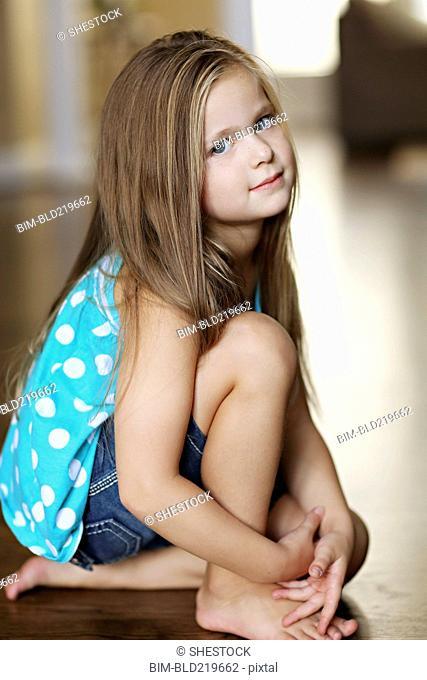 Serious girl sitting on floor