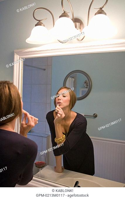 Young Caucasian woman applying lip gloss in bathroom mirror