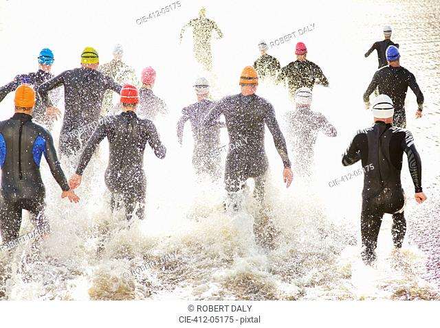 Triathletes in Tri suits running into ocean