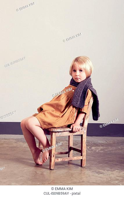 Portrait of sullen girl sitting on old wooden chair
