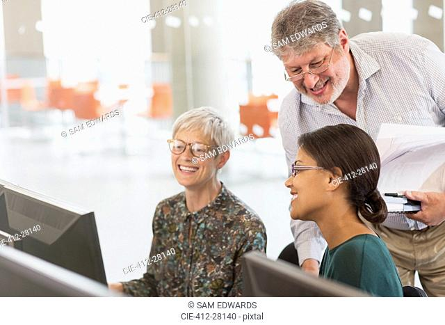 Smiling students talking at computer in adult education classroom