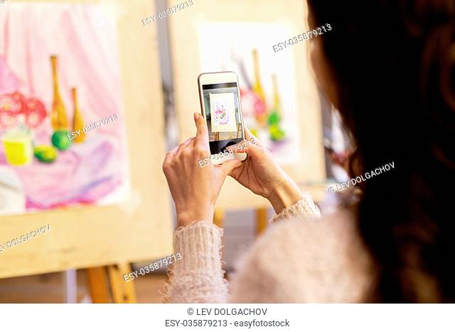 technologyl, creativity and people concept - woman artist or student with smartphone photographing still life painting or picture at art school studio
