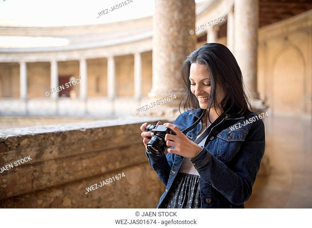 Spain, Granada, smiling young woman looking at camera at the Alhambra