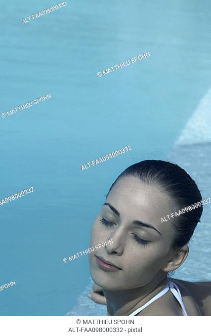Young woman in swimming pool, eyes closed