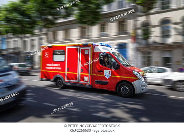 French emergency vehicle rushing through city street with blue lights flashing