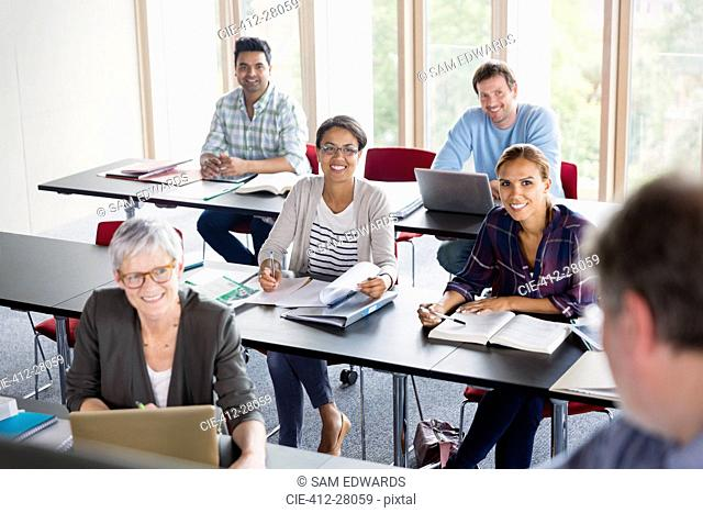 Smiling students watching teacher in adult education classroom