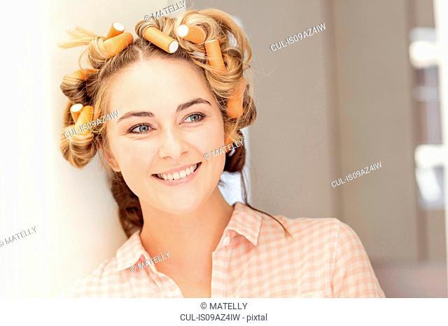 Portrait of young woman wearing foam rollers in hair