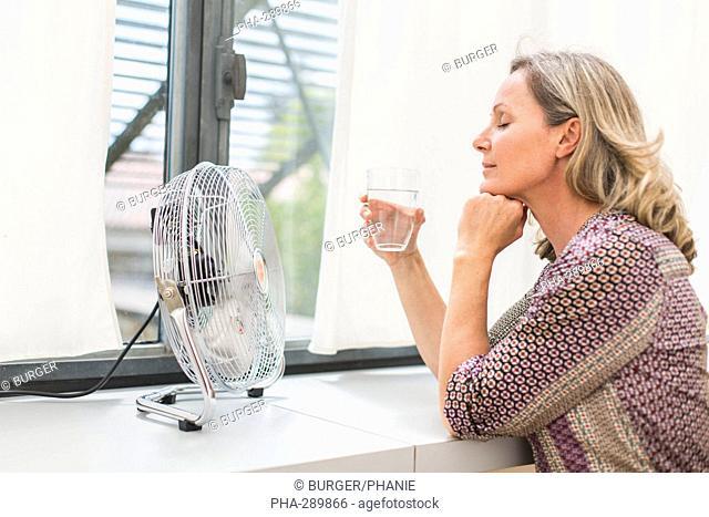 Woman using an electric fan