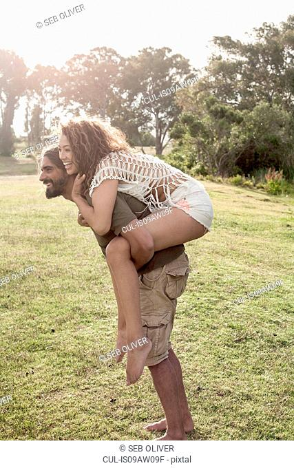 Side view of young man bending forward giving young woman piggyback smiling