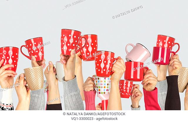 many raised hands up with ceramic cups on a white background, recruitment concept, join our team