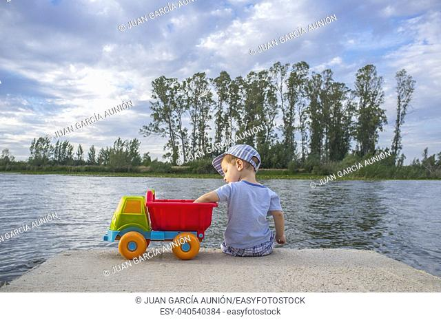 Two year old boy playing at riverside with dump truck. He is sitting over fisher platform throwing stones