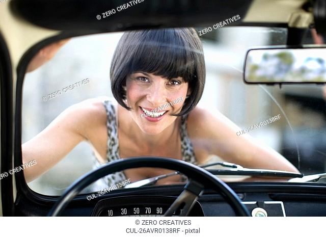 Woman laying on the front of a car