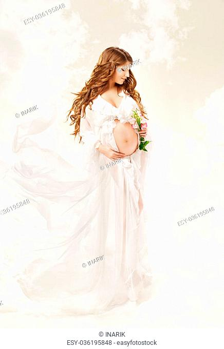 Pregnant woman. Beautiful pregnancy: long curly hair and chiffon dress fluttering on wind