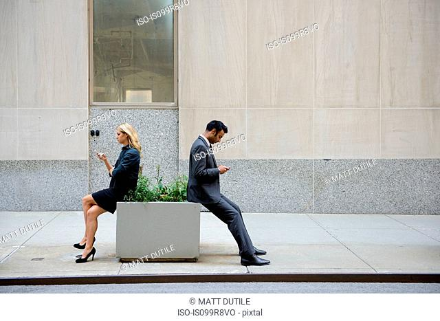 Businesspeople sitting and looking at cellphones outdoors