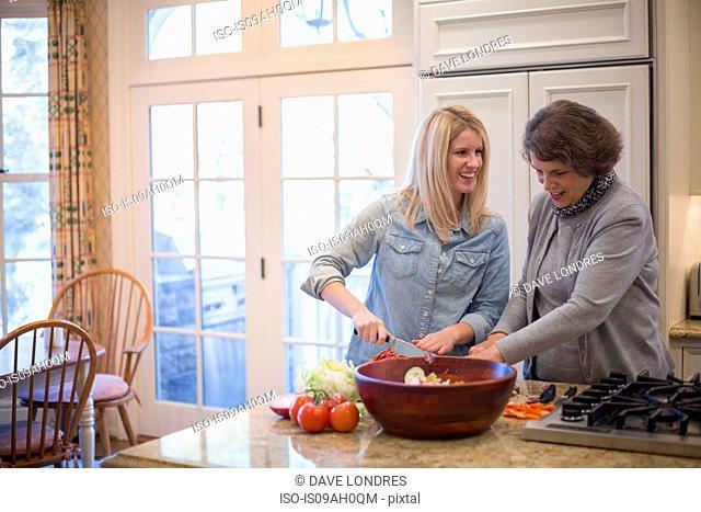 Senior woman and granddaughter preparing salad