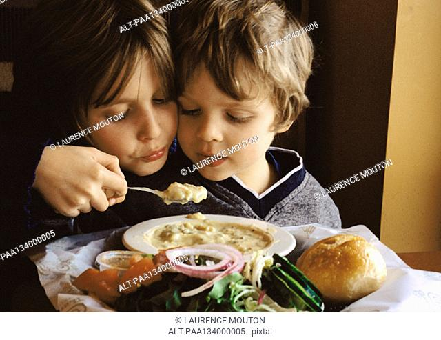 Young boy helping younger brother eat, portrait