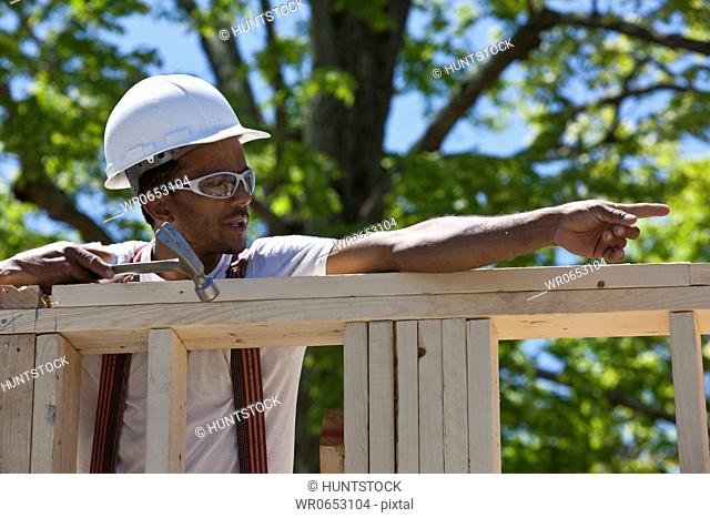 Carpenter working on a frame at a construction site