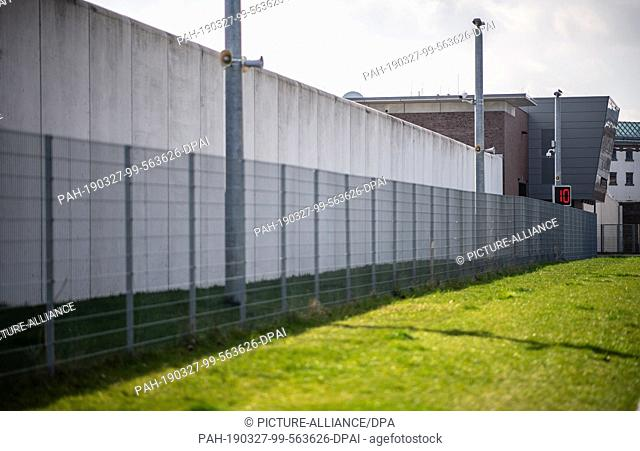 27 March 2019, North Rhine-Westphalia, Werl: A fence stands in front of the prison wall along the main gate of the prison (JVA) Werl