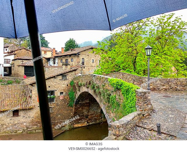 Old bridge in Potes in a rainy day with an umbrella. Potes, Cantabria, Spain