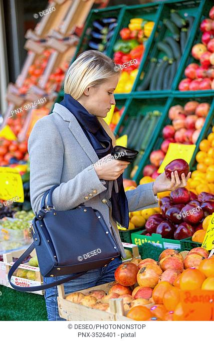 Pretty blonde woman buying healthy food on the market