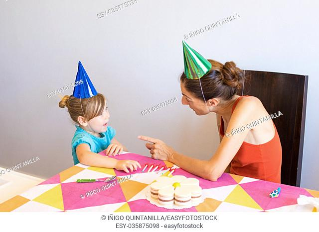 woman with orange sleeveless top talking to three years old blonde child blue shirt, at birthday party, with colored cone caps