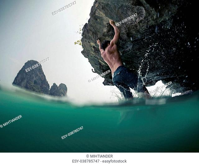 Young man trying to climb natural wall without belay. Deep water soloing