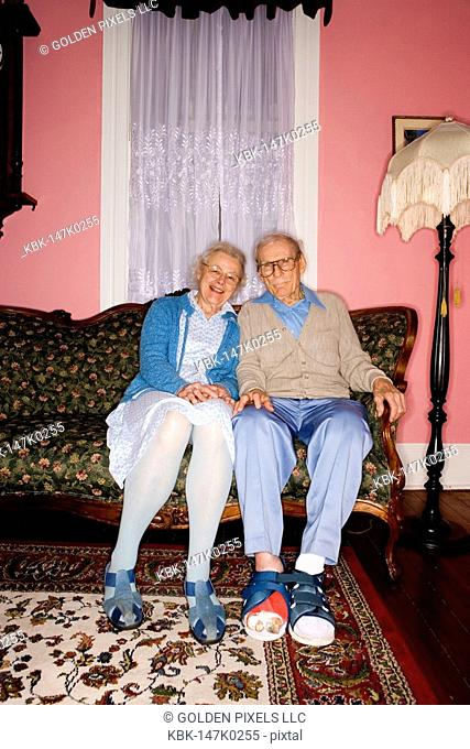 Portrait of cheerful senior couple sitting and separated on sofa in living room