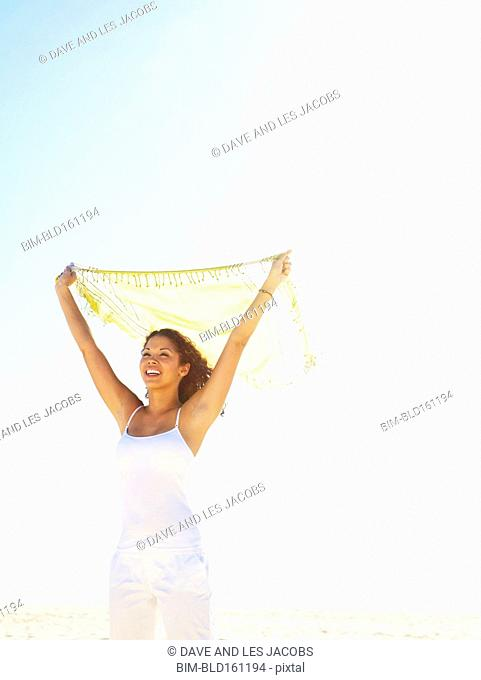 Mixed race woman holding fabric under sunny sky