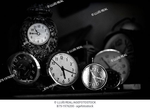 clocks and alarm clocks on a shelf