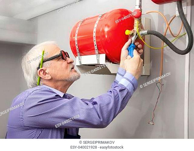 Man sets a fixed fire extinguisher