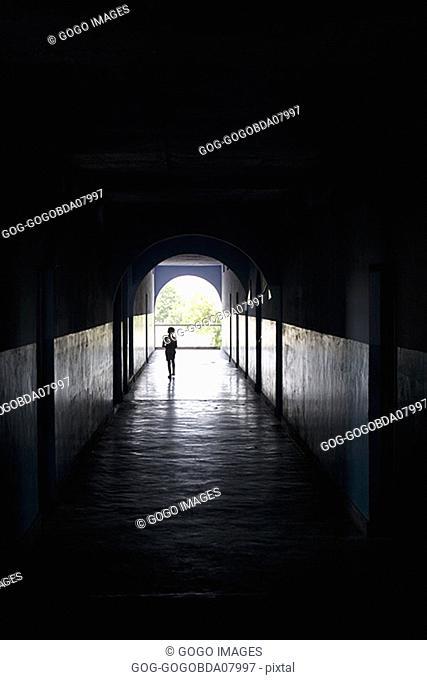 Child walking through a dark hallway